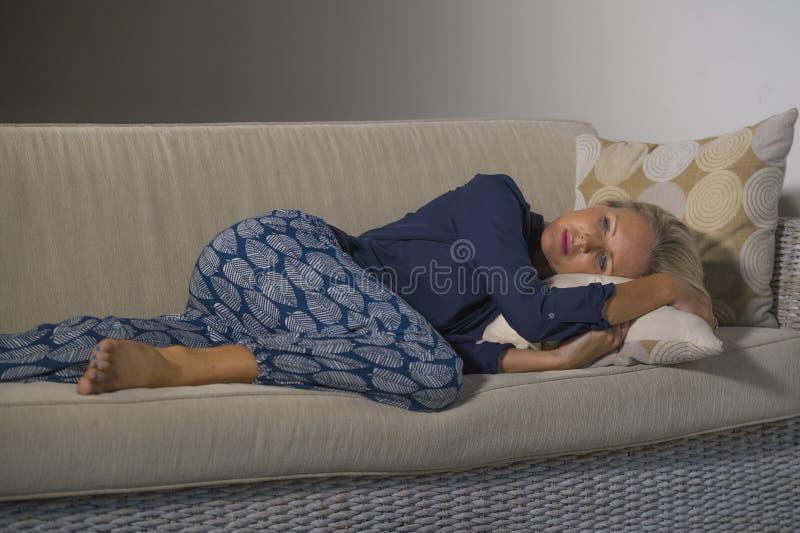 沮丧和急切美丽的白肤金发的感觉妇女遭受的消沉被挫败的和偏僻在家说谎沙发长沙发thoughtfu 免版税库存照片