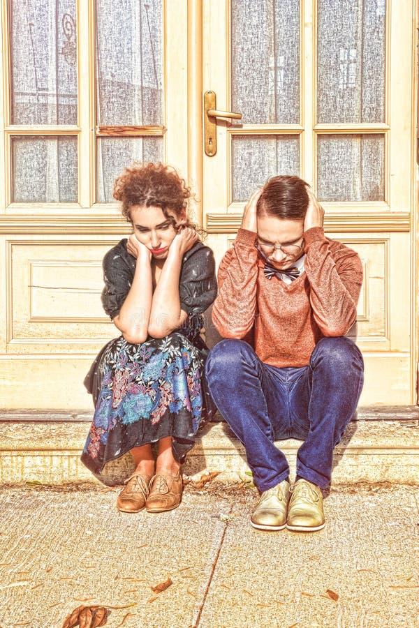 沮丧和搅动的蹲下在h前面的男人和妇女 图库摄影