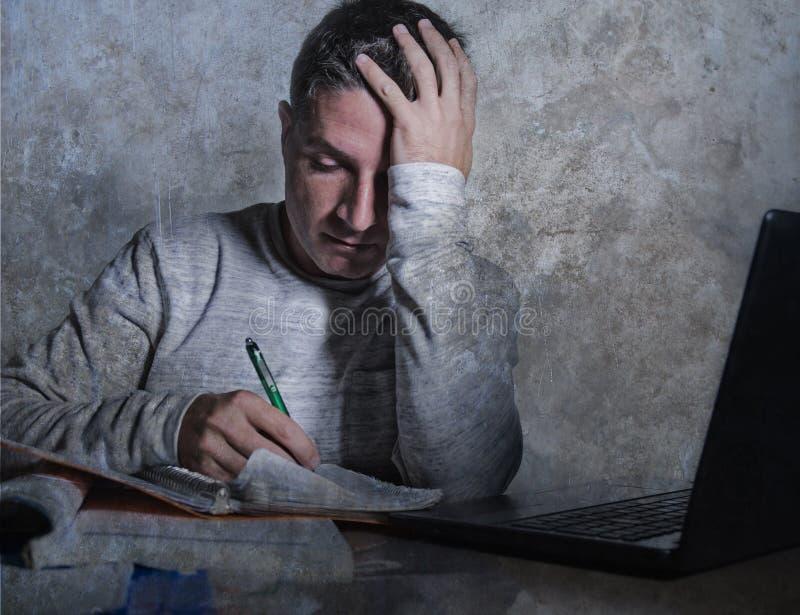 沮丧和被注重的年轻大学生人与课本笔记薄和便携式计算机书桌感觉一起使用在家淹没 库存图片