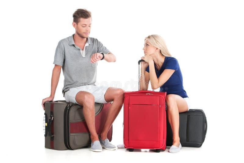 沮丧的与行李的夫妇等待的离开 免版税库存图片