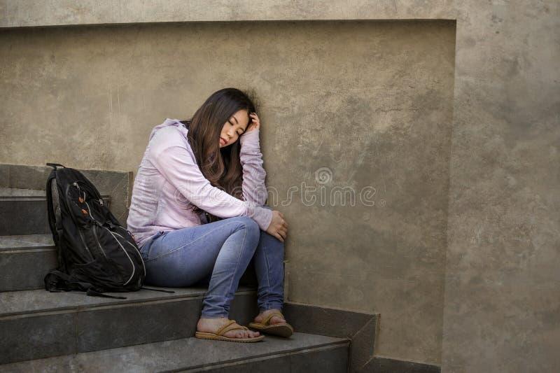 沮丧的亚裔韩国学生妇女或被胁迫的少年户外坐街道楼梯被淹没的和急切感觉 库存图片