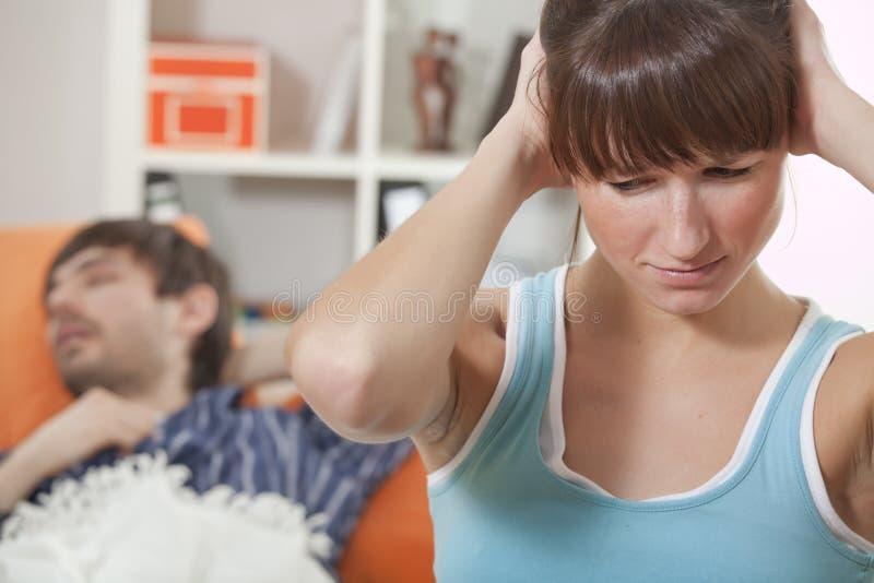 沮丧的人打鼾的妇女 免版税库存照片