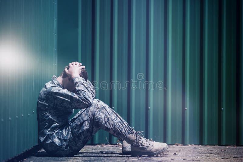沮丧的军事战士用手坐头 免版税图库摄影