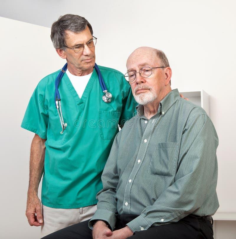 沮丧的医生男性护士耐心的前辈 免版税图库摄影