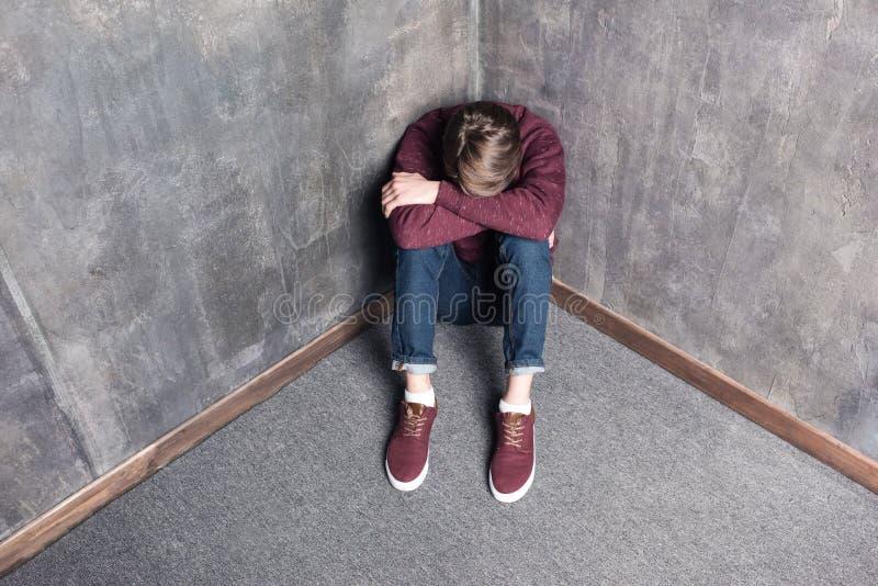 沮丧的十几岁的男孩坐地板 免版税库存照片