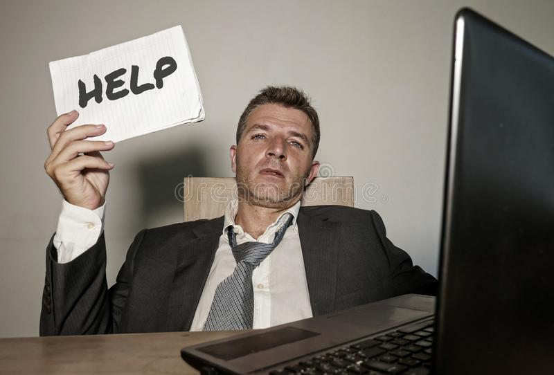 沮丧的商人绝望在办公计算机书桌与hashtag仿造仿造的藏品笔记薄作为被剥削的雇员 免版税库存照片