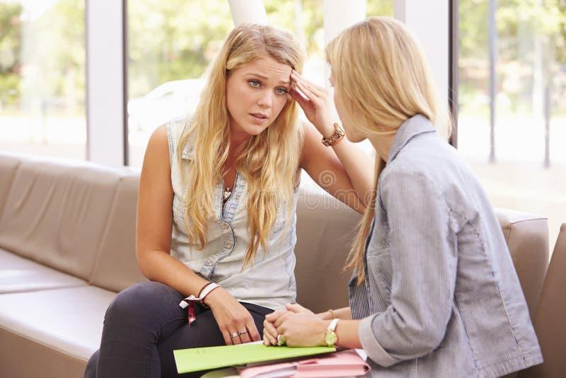 沮丧的大学生谈话与顾问 免版税库存照片