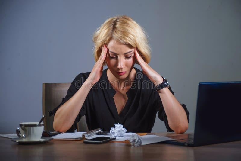沮丧的女商人工作被淹没在办公室充满便携式计算机感觉用尽了拿着她的头的遭受的头疼 库存图片