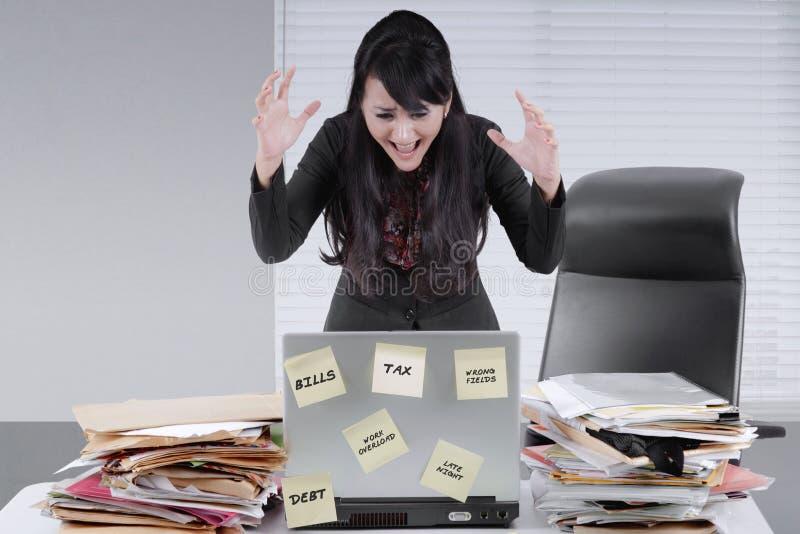 沮丧的女实业家尖叫对她的膝上型计算机 免版税库存图片