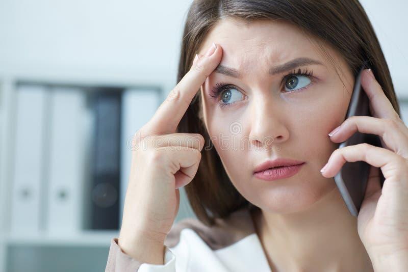 沮丧的女实业家谈话在电话,当研究计算机在书桌在办公室时 图库摄影
