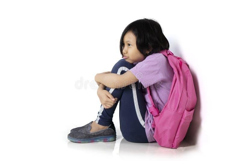 沮丧的女小学生在演播室坐 免版税库存照片