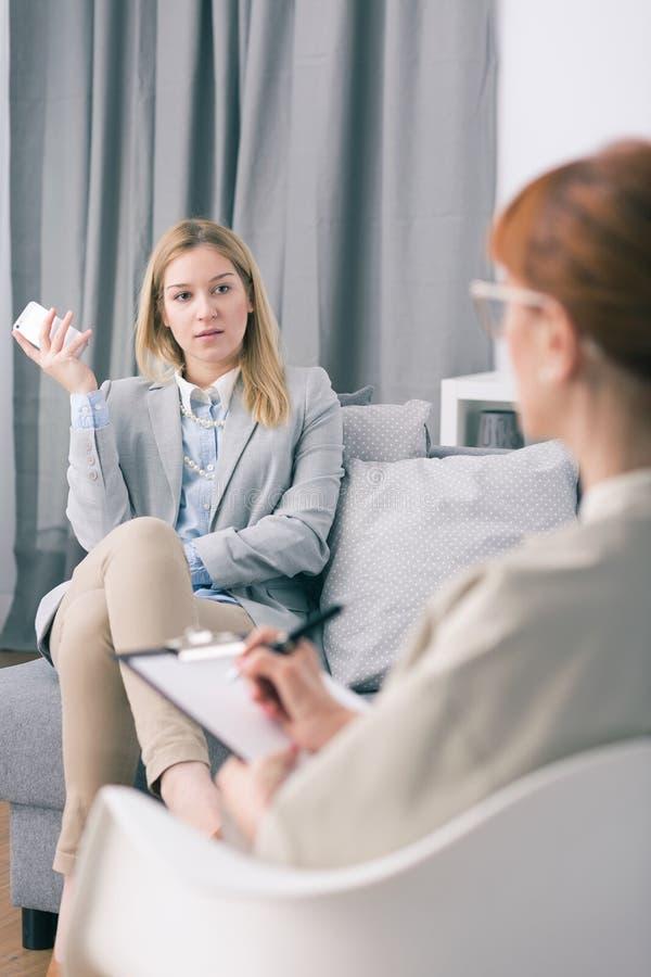 沮丧的妇女拿着电话和谈话与她的心理学家 免版税库存照片