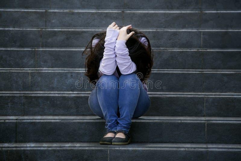 沮丧的学生妇女或被胁迫的少年女孩户外坐胁迫的街道楼梯害怕的和急切受害者 免版税库存图片