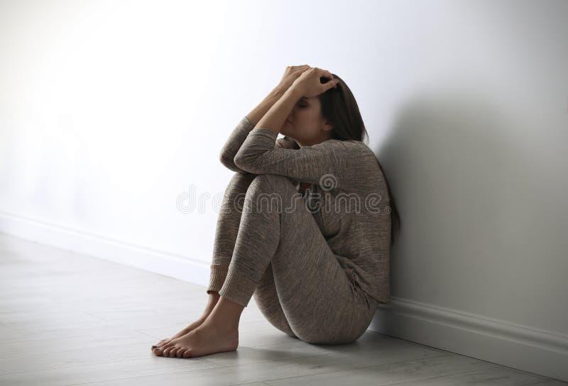 沮丧的少妇坐地板 免版税库存照片