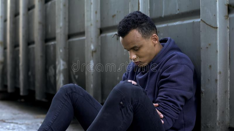 沮丧的少年坐在门户的,失踪的孩子,从父母的逃命 免版税库存照片