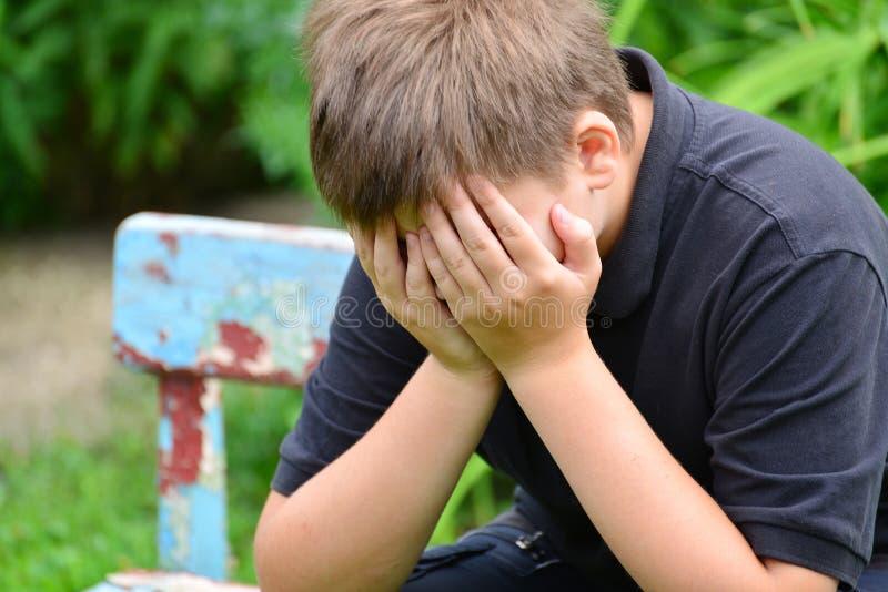 沮丧的少年坐长凳 库存图片