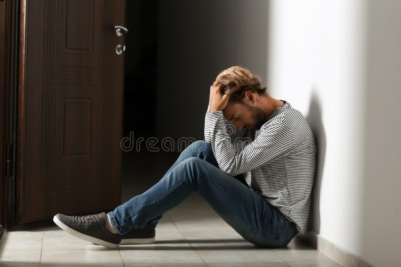 沮丧的年轻人坐在黑暗的走廊的地板 图库摄影