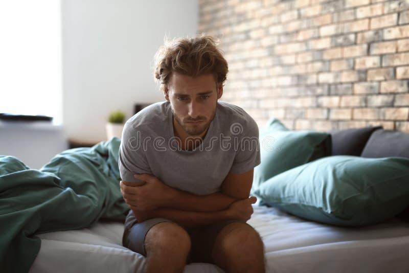 沮丧的年轻人坐床 免版税库存图片