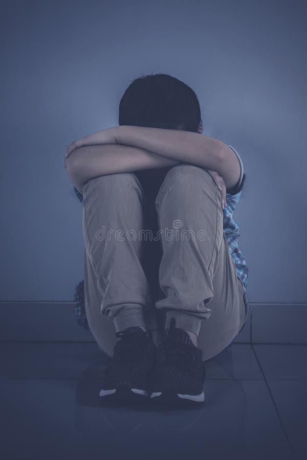 沮丧的年轻男孩坐地板 库存照片