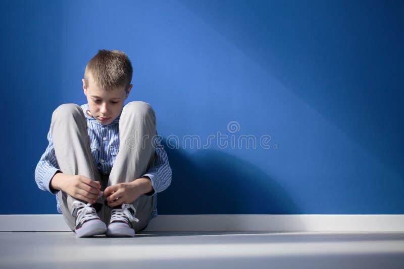 沮丧的男孩在屋子里 库存图片