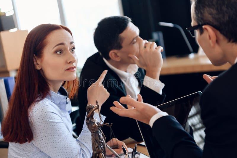 沮丧的红发妇女把手指指向转向其他方式的成人人,在律师` s办公室 库存图片