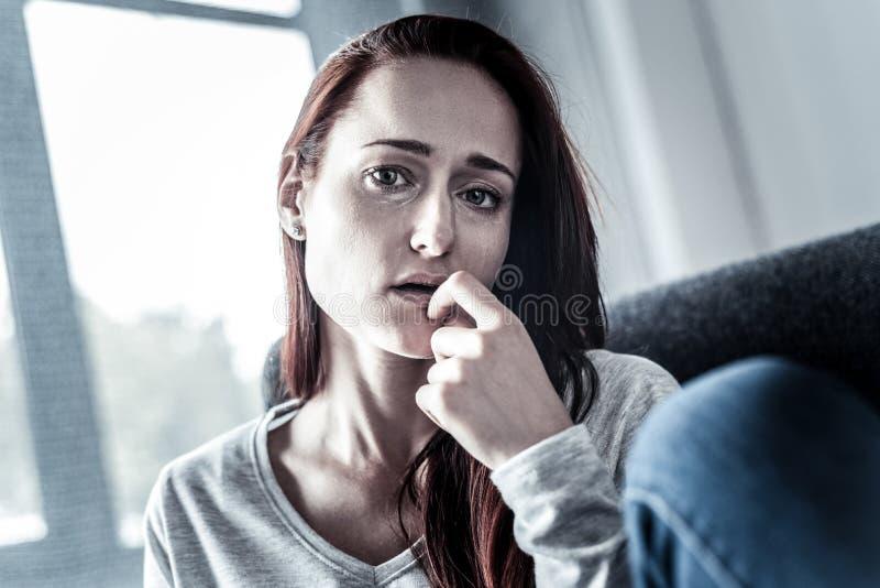 沮丧的翻倒妇女感觉床和看直接 图库摄影