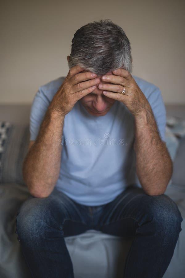 沮丧的老人坐沙发 图库摄影