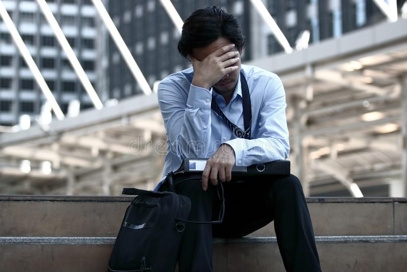 沮丧的被注重的年轻亚洲商人感人的头和关闭画象他的眼睛 他感觉张力或尝试和heada 免版税库存照片