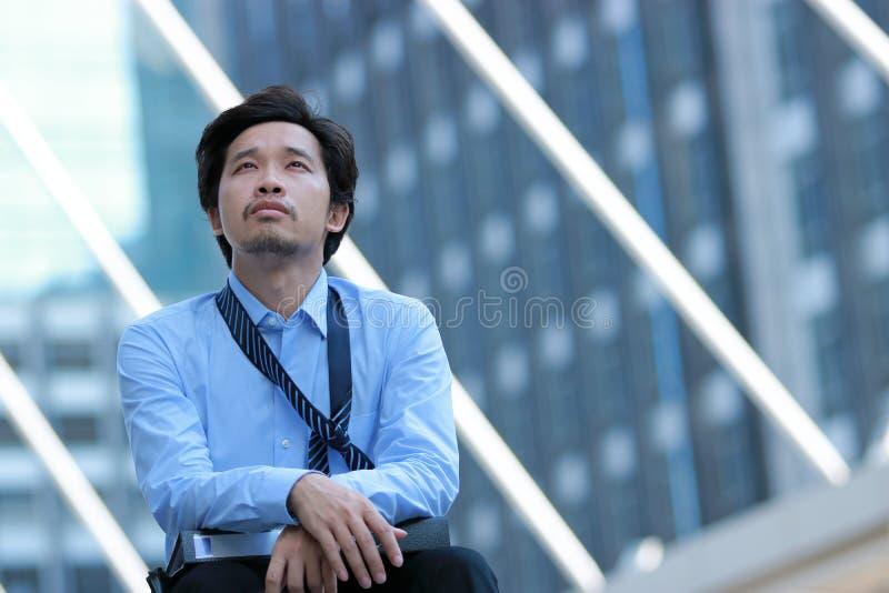 沮丧的被注重的年轻亚洲商人感觉被用尽和头疼反对工作在与拷贝空间backgroun的都市大厦 免版税库存照片