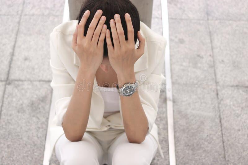 沮丧的被注重的年轻亚洲女商人覆盖物面孔用遭受麻烦的手 免版税库存图片