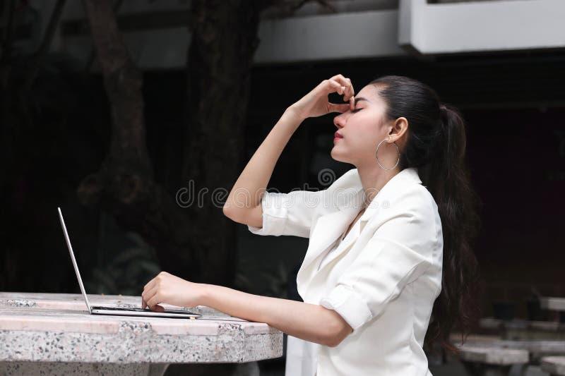 沮丧的被注重的年轻亚洲女商人覆盖物面孔用遭受麻烦的手 库存图片
