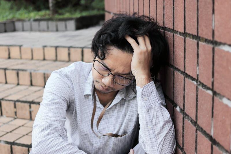 沮丧的被注重的年轻亚裔人感人的头和感觉失望或用尽 失业的商人概念 免版税库存照片