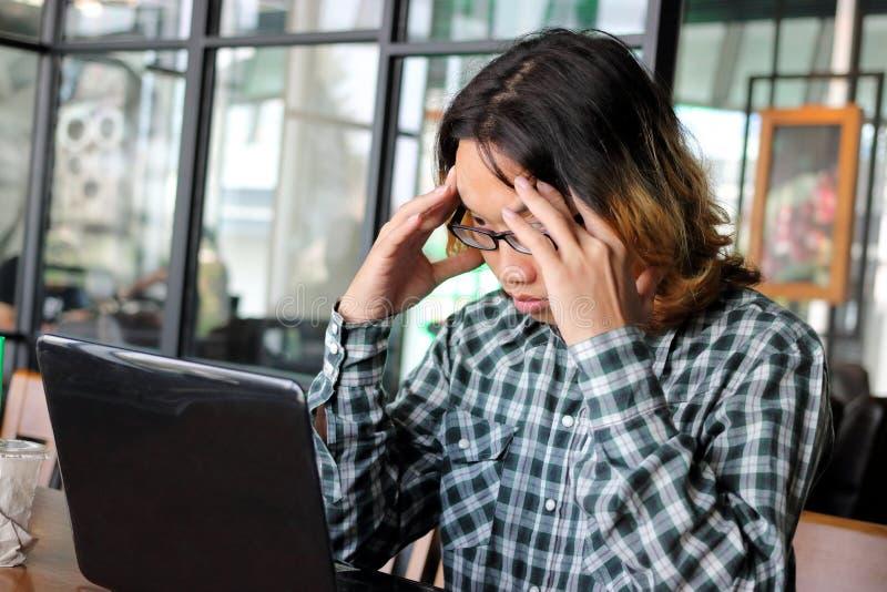 沮丧的被注重的年轻亚裔商人用在顶头感觉的手疲倦了或失望了反对他的工作在办公室 Exhauste 免版税库存照片