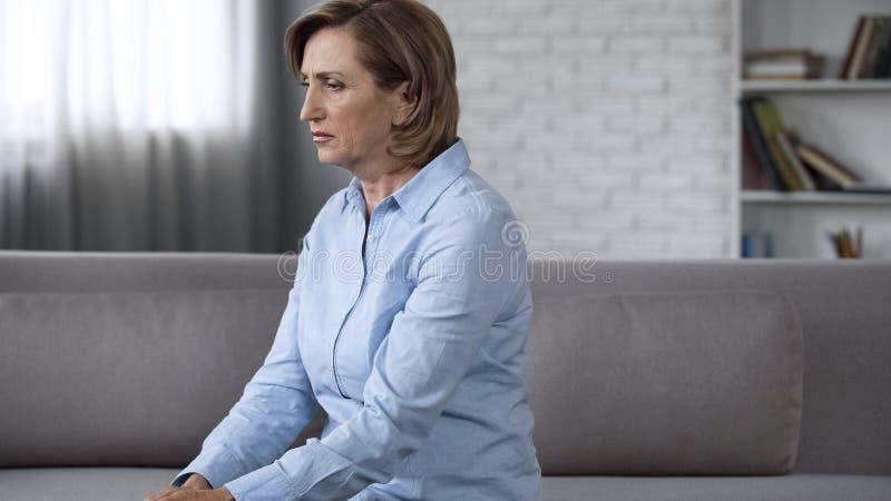 沮丧的资深夫人坐长沙发,感觉急切,心理问题 免版税图库摄影