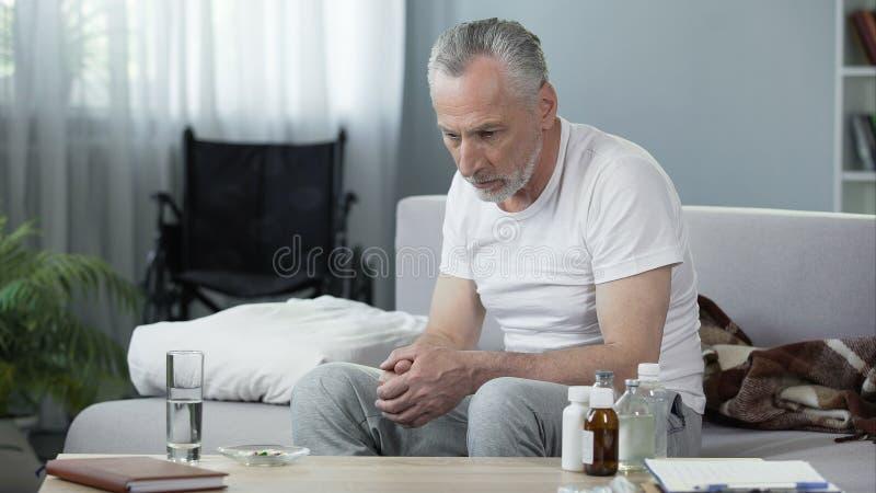 沮丧的资深男性坐沙发在老人院、寂寞和忧郁 免版税库存图片