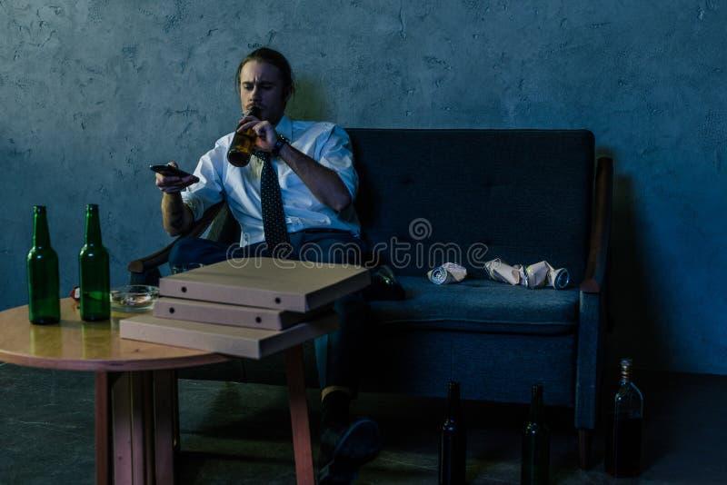 沮丧的酒精使白色衬衣的人上瘾看电视和喝啤酒的 免版税库存图片