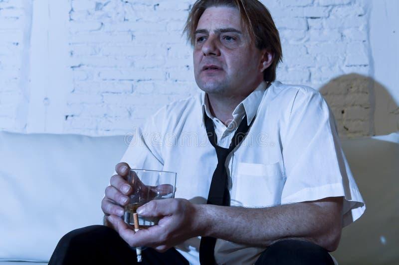沮丧的酒精商人用宽松领带被浪费的和被喝的饮用的威士忌酒 免版税库存图片