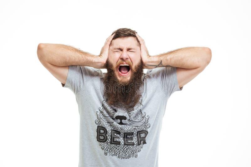 沮丧的翻倒有胡子的人用人工和呼喊盖了耳朵 免版税库存照片