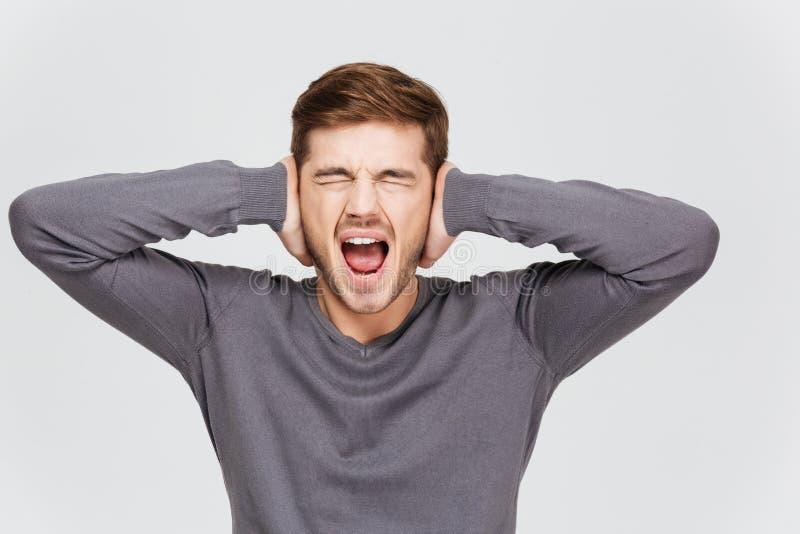 沮丧的翻倒年轻人用手报道了耳朵和呼喊 免版税库存照片