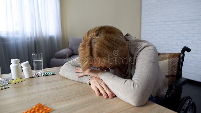 沮丧老女性哭泣在桌、健康问题、消沉和寂寞上 库存图片