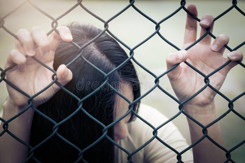 沮丧,麻烦和解答 在链子链接篱芭的绝望的妇女手 库存图片