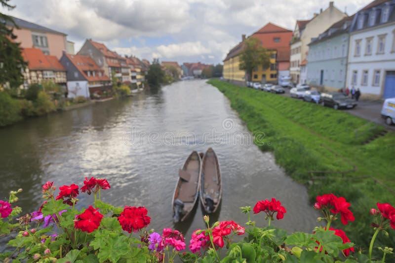 河、小船、红色花和葡萄酒房子 库存照片