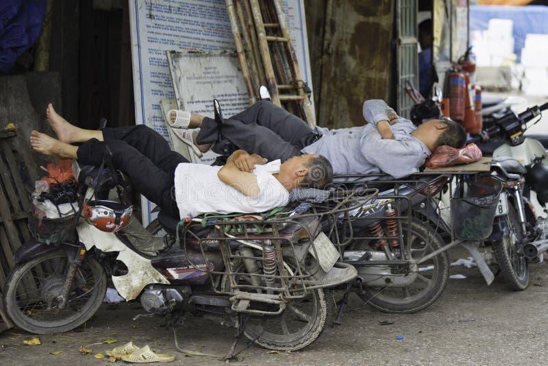 河内,越南- 2015年8月28日:摩托车驾驶员睡觉在午餐时间在长的比恩市场上 库存照片
