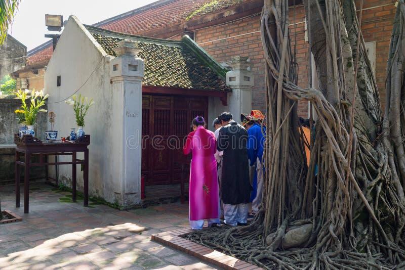 河内,越南- 2016年7月24日:穿老传统长的礼服Ao戴的京族祈祷在第五个法院的小寺庙 免版税库存照片