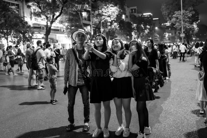 河内,越南- 2018年4月13日:青年人在河内交通镇定的地区采取selfie  图库摄影