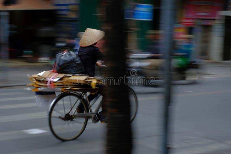 河内/越南,05/11/2017:自行车的越南妇女有在一条繁忙的忙碌路的传统米帽子的有通过的汽车和 免版税库存照片