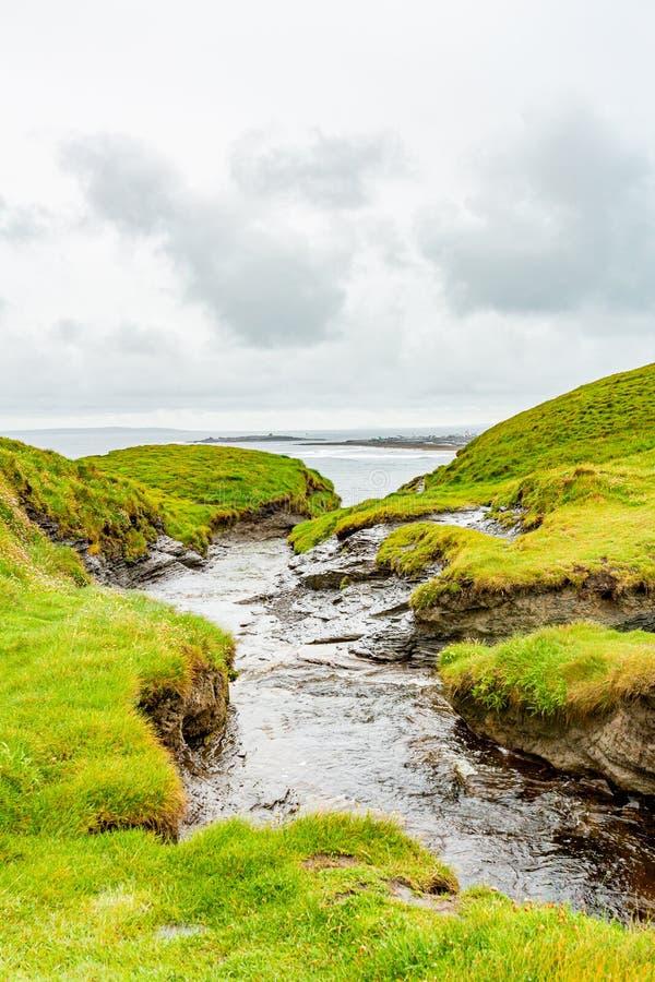 河口到有Doolin和螃蟹海岛口岸的海里在背景中 免版税库存图片