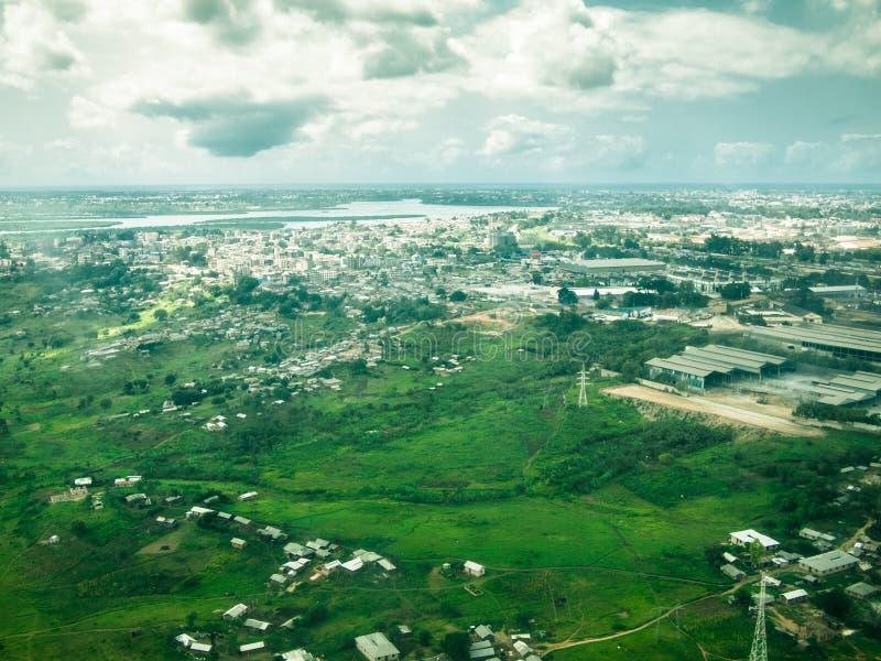 从河和沼泽地森林的飞机的窗口的被定调子的图象有市的蒙巴萨在背景中与天空 免版税库存照片