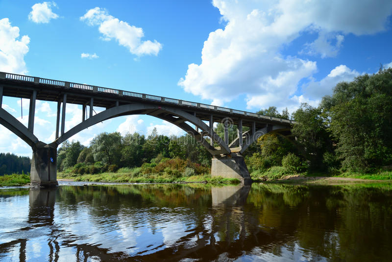 河和通过云彩在桥梁 免版税库存照片