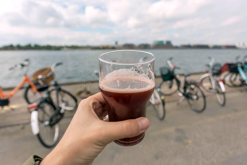 河岸和手有啤酒杯的 城市哥本哈根,丹麦的中心 丹麦首都自行车和乐趣时间 免版税图库摄影